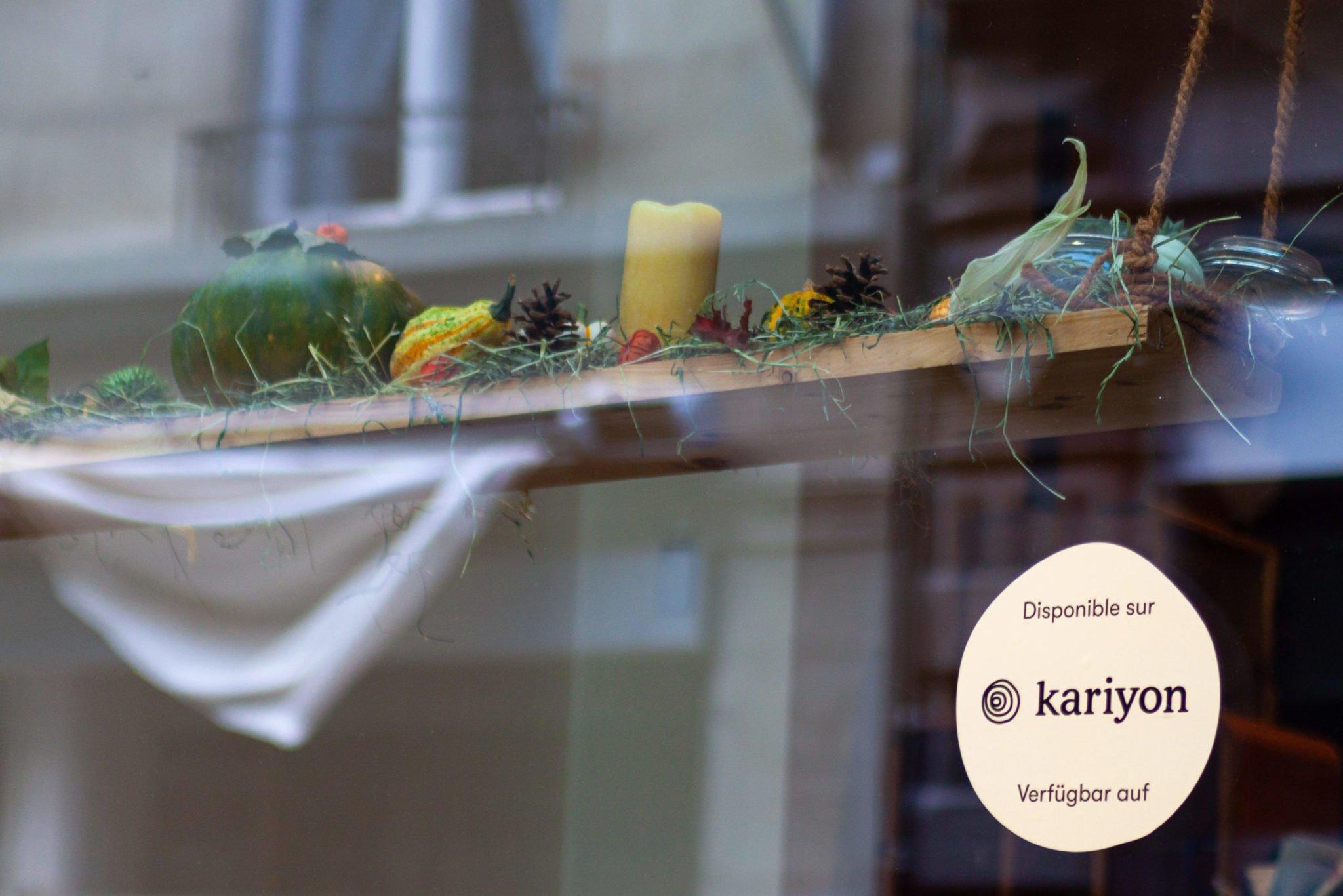 Photo d'un autocollant Kariyon colé sur une vitrine de commerce.